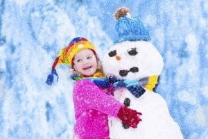 Happy little girl playing with a snowman