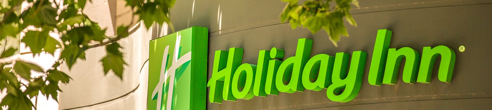 Exterior sign of Holiday Inn Melbourne with tree leaves around it