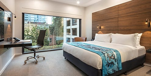 Poolside guestroom with 2 double bed, work desk & sofa chair near wall to ceiling window